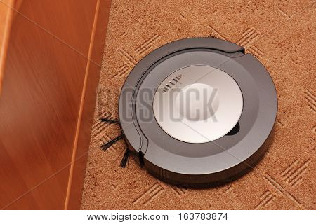Small robotic vacuum cleaner sucking the brown carpet
