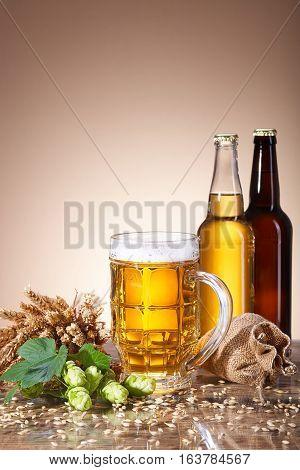Assortment of fresh beer in bottles, ears of wheat, ripe fruit hops, with beer mug, brewing ingredients, bag of ripe grain