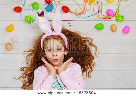 Curly girl wearing bunny ears on Easter spring holiday background.