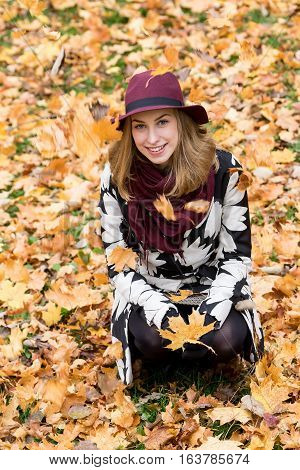 Woman in a floral patterned coat and wine red hat playing with leaves in the park. Happy girl throws maple tree leaves into the air. Yellow green red and brown leaves colorful autumn forest