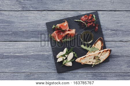 Catering platter antipasto with ham prosciutto, bruschetta bread toasts and mozzarella cheese on stone desk on blue wood table top view with copy space. Served starter meals, restaurant food