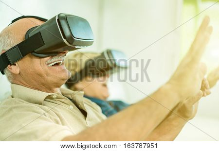 Senior mature couple having fun with virtual reality glasses - Old people using new headset goggles trends technology - New mania trends addiction - Focus on man headset - Warm greenery filtered look