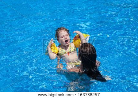 three years old blonde child in yellow bikini with floater sleeves in arms and complain face rising up in mother hands in blue water of swimming pool