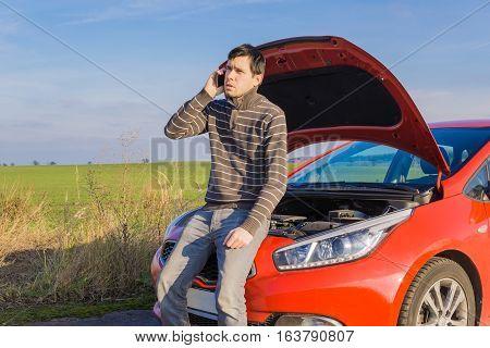 Car is broken man is calling assistance.