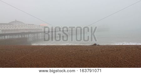 View of Brighton beach and Pier in a misty rainy day.