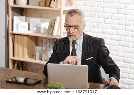 Dealing with issues. Attractive thoughtful mature man sitting at his office desk and carefully reading something on his laptop