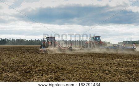 a tractor working in a field plowed soil