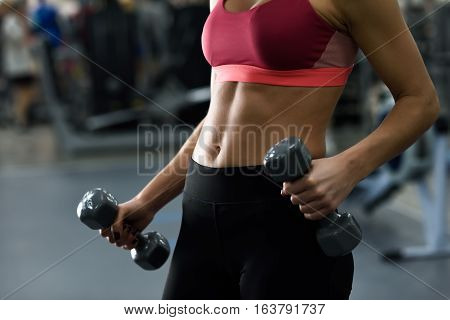 Young Woman With Beautiful Abdomen Lifting Dumbells At Gym