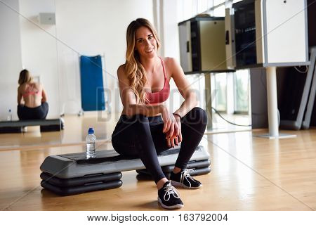 Young Woman In Sportswear Holding An Apple At Gym