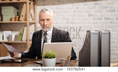 Organized workplace. Attractive serious elderly entrepreneur sitting at his desk in an office and thoroughly reading documentation while being photographed