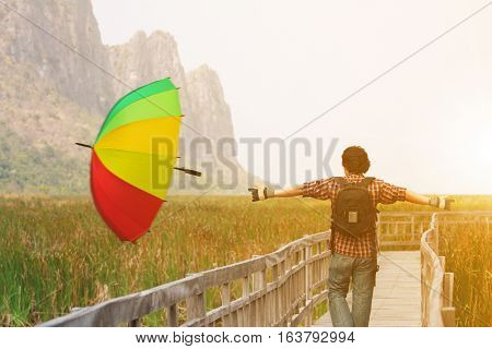 beautiful landscape with freedom people or tourist happy relax and wear gloves winter with leaving a rainbow umbrella for rainy season leave and welcome winter season on vintage wood bridge in meadow
