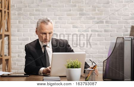 New message. Concentrated professional senior businessman using his laptop to write a letter while sitting in his office at his desk
