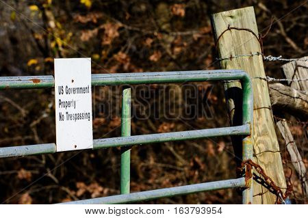 US Government Property sign on locked gate with thick woods in background