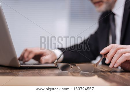 I need these. Neat well dressed qualified office worker reaching his hand to take a pair of glasses while working on his laptop at the