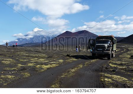 TOLBACHIK VOLCANO KAMCHATKA PENINSULA RUSSIA - AUG 27 2014: Russian extreme off-road expedition truck ZIL-131 (6-wheel drive) on mountain road on background of volcanic cinder cone and beautiful volcano. Kamchatka Klyuchevskaya Group of Volcanoes