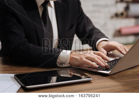 Neat and clean. Well dressed focused senior office worker using his computer and typing a current report while sitting at the desk in his office