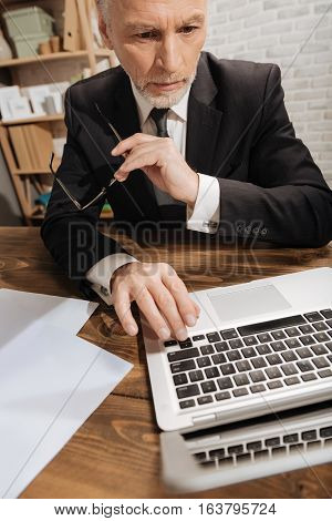 Highlighting some articles. Professional attractive mature gentleman reading a document using his computer while holding his glasses and sitting at the table in office