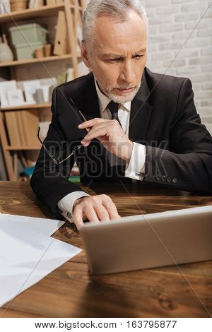 This figure does not look good. Determined thoughtful senior gentleman looking through a contract using his laptop while sitting at the table in his office