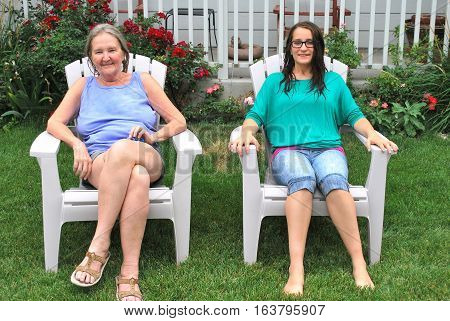 Grandmother and grand daughter relaxing outside sitting in lawn chairs.