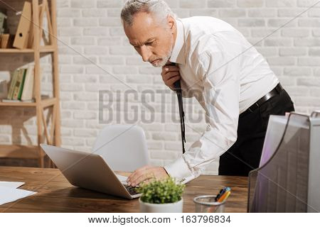 Bad news. Upset serious nervous businessman looking at the screen of his computer and hitting some buttons while fixing his tie