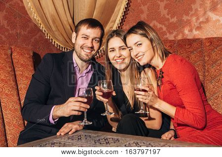group of friends resting in the restaurant, smile at the camera, two women and one man