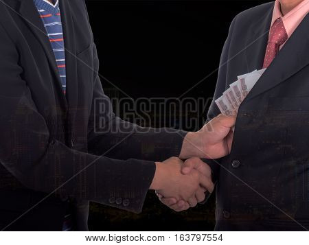 Double exposure of businessman giving a bribe to the pocket with cityscape night light background. Corruption and fraud concepts