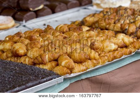 Tray full of croissants among other pastries products.