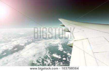 Wing plane and travel plane concept.Flying over the clouds.Sunset and plane