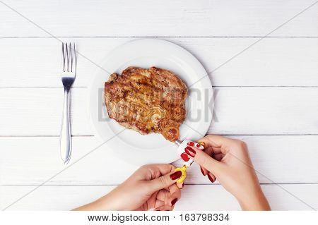 Concept photo: food from a tube. Not healthy food. genetically modified food. Woman's hands push real meat steak from the tube. Photo composing.