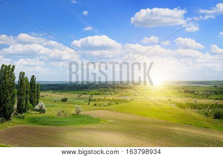 hilly terrain spring field and sunrise on blue sky