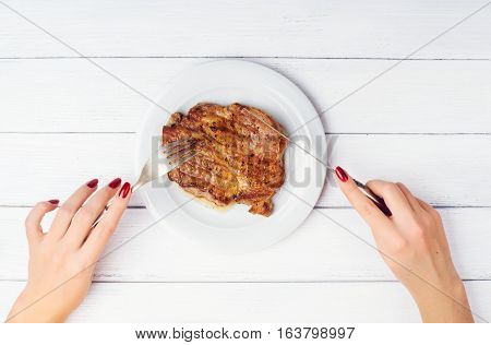 Woman's hands cuts delicious beef steak on white plate with fork and knife on white wooden background with space for text. High key.
