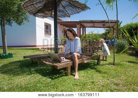 brunette woman with white shirt and jeans shorts barefoot sitting on lounge deck chair using laptop and two years old blonde child at garden