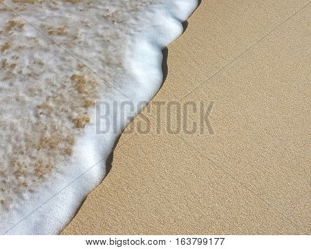Closeup of foamy wave bathing the sand on the beach shore in the Caribbean.
