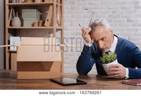 What was the wrong move. Thoughtful worried elderly businessman trying analyzing his false steps after being dismissed while sitting at his table with packed away things