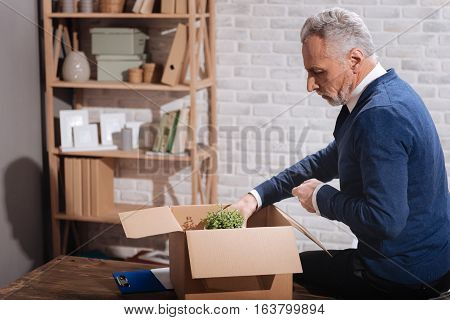 Last items. Handsome upset mature businessman putting away his things after learning about his retirement while leaving his office