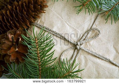 Gift wrapped craft paper with pine cones and fir branches, top view, New Year concept