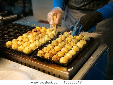 Woman Process To Cooking Takoyaki At Night Maket. It Most Popular Delicious Snack Of Japan.