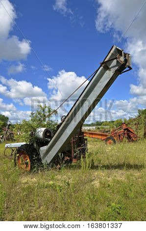 An old junked one row corn picker