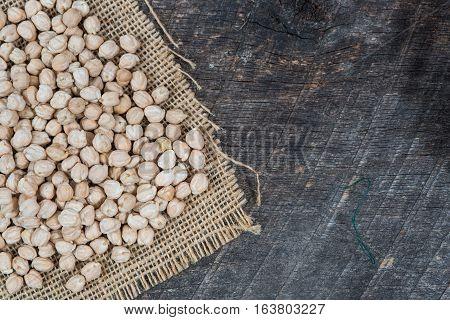 Chick peas on burlap napkin on olden wood board