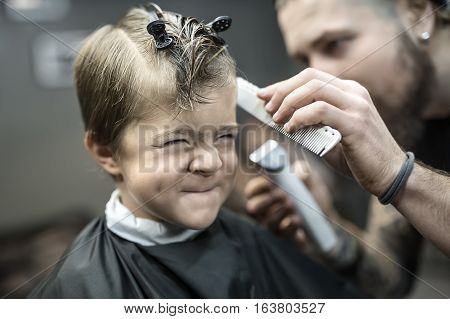 Laughing little boy with closed eyes in the black salon cape in the barbershop. Bearded barber makes a hairstyle with a trimmer and a comb. Low aperture closeup photo. Horizontal.