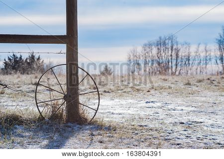 Wagon wheel leaning against a fence looking out a field covered in snow.
