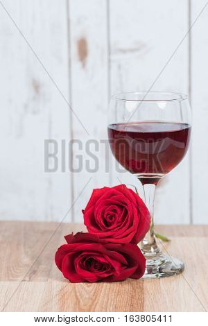 Wine with roses on wooden background and  table