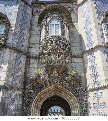 Portugal Sintra . Castle Pena Triton over the lancet arch leading to the courtyard of the castle supports the balcony. The figure is decorated with real sea shells and coral.
