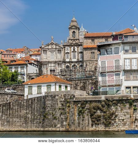 Portugal Porto . Residential homes on the embankment of the River Duero on the background of the church of Saint Francisco .