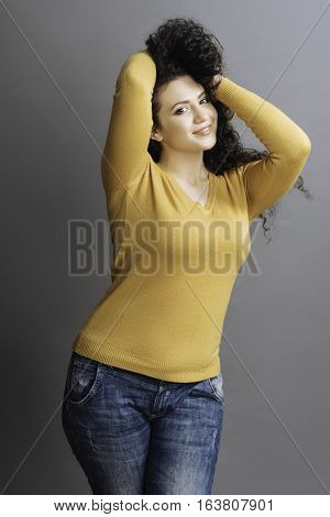 Joyful mood. Delighted young woman touching her curly hair with both hands posing at camera while standing isolated on grey background