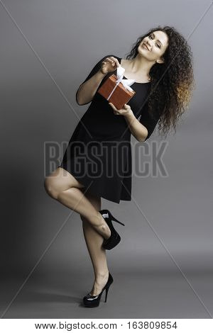 I like this. Happy woman wearing black dress and high-heeled shoes standing in semi position holding her left leg bent in knee over grey background