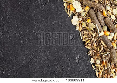 dry food for rodents on dark background top view.