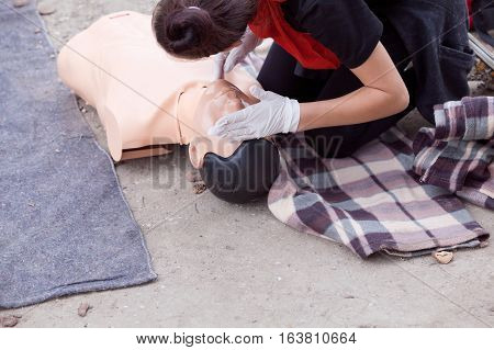 Checking heart rate. Female instructor showing cardiopulmonary resuscitation - CPR on training dummy. First aid training.
