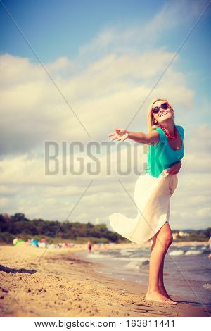 Summer time relax leisure concept. Attractive woman on the beach. Lady wearing sunglasses having fun on sunny day