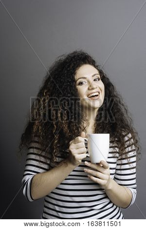 Have a coffee break. Young woman with curly hair smiling handing a cup of coffee in both hands, looking at photographer
